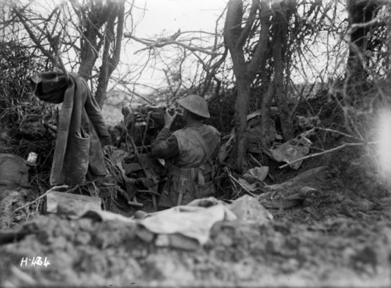 New Zealand soldier using a captured machine gun at the front line at La Synge Farm, France, during World War I.